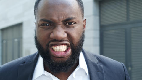 Businessman making angry grimace at camera. Businessman standing on street Live Action