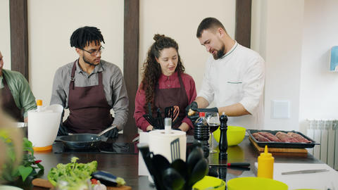 Diverse group of cookery students talking to chef watching him preparing meal Live Action