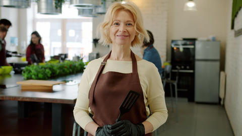 Portrait of cheerful adult woman smiling wearing apron at cooking class indoors Live Action