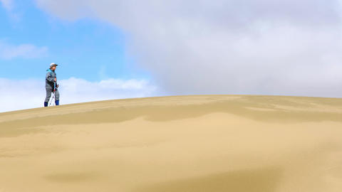 Tourist Walking Along the Edge of the Sand Dune Live Action
