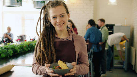 Portrait of pretty girl standing in cooking school with delicious dish smiling Live Action