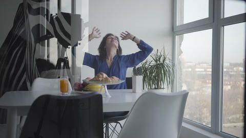 Studio shot of happy adult Caucasian woman having breakfast in the morning Live Action