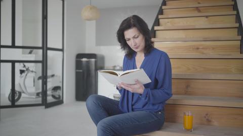 Portrait of intelligent gorgeous woman reading book indoors. Brunette Caucasian Live Action