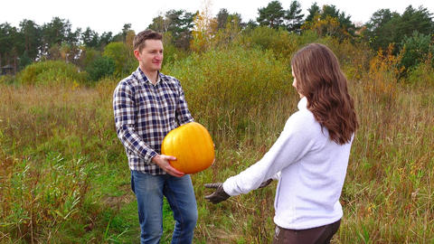 Man bring big pumpkin and give wife, woman take large squash with difficulty Footage