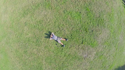 Zoom-in aerial vertical view of young guy sleeping on grass Footage