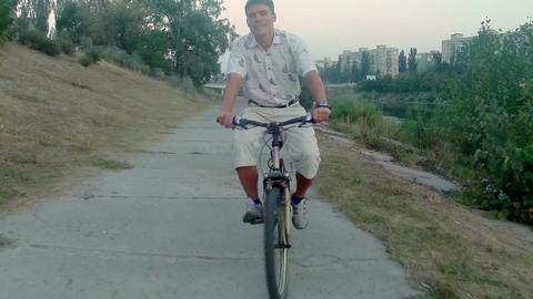 Smiling man riding bicycle, city park near river, aerial shot Footage