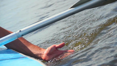 Male hand entering clear water, cold sensation. Rowing boat Footage