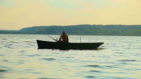 Silhouette of lone fisherman sitting in boat, fishing equipment Footage
