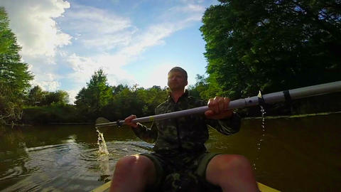 Young man paddling canoe on river. Action camera, slowmotion Footage