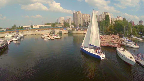 Yacht making turn in small city harbor. Yachting, sailing, sport Footage