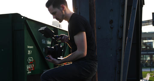 Male young Filmmaker in black with beard film handheld the sunset. Business Live Action
