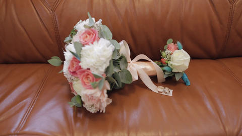 Beautiful wedding flower bouquets lie with wedding rings on brown sofa Live Action