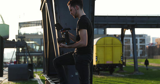 Handsome Male young caucasian Filmmaker in black with beard film handheld Live Action