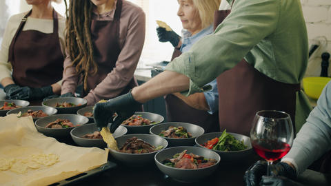 Diverse group of joyful people preparing and serving tasty meals in cookery Live Action