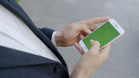Businessman browsing internet on phone outside. professional using cellphone Live Action