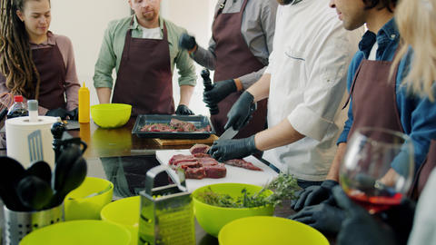 Happy youth learning cooking secrets during master-class by professional chef Live Action