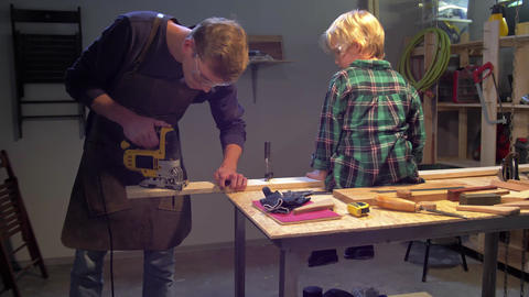 Boy sits on board, man screws a nail into a board on a table Live Action