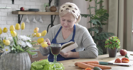 Portrait of calm Caucasian senior woman reading book and drinking red wine in Live Action