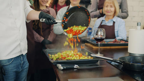 Tilt-up of cheerful chef teaching group of trainees cooking vegetables in Live Action