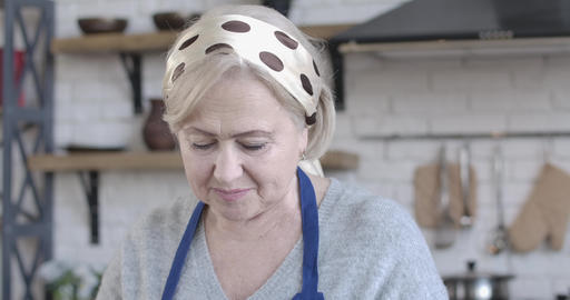 Close-up face of beautiful senior Caucasian woman cooking indoors. Cheerful Live Action