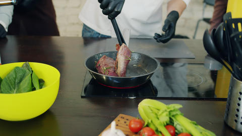 Skilled male chef cooking meat in frying pan working with group of people Live Action