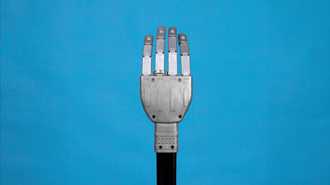 A mechanical arm bends fingers and shows a ring finger with a ring. Gray cyborg Live Action