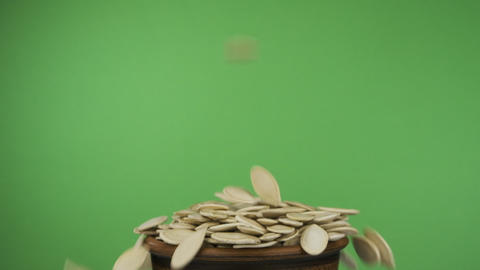 Pumpkin seeds fall into a crowded clay bowl and fall out of it. Isolated on a Live Action