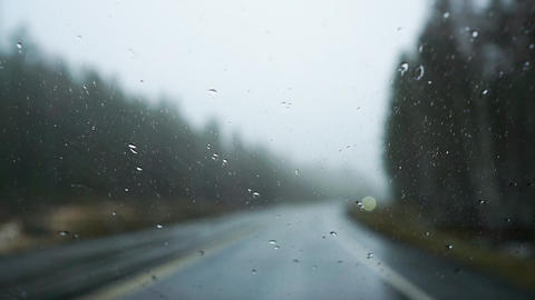 Raindrops on windscreen blurry cars passing by driving on road in Finland Live Action