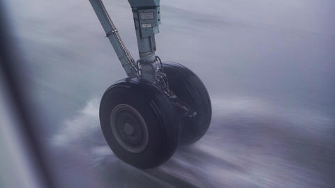 Airplane landing gear taxiing the runway in heavy rain Live Action