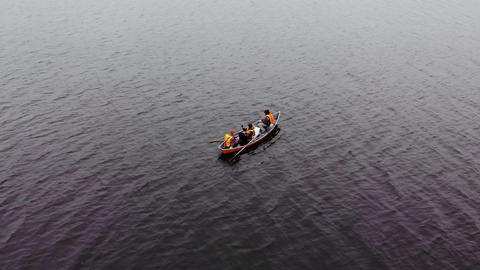 Three men in orange life jackets fishing in orange boat on lake in Finland bird eye view Live Action