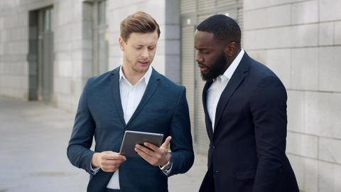 Businessmen using digital tablet on city. Male entrepreneurs talking outdoors Live Action