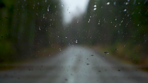 Raindrops on windscreen driving on bumpy gravel road in Finland in autunm Live Action