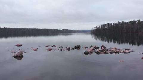 Stones scattered in water on Finland lake aerial forward shot Live Action