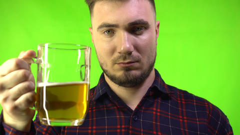 Drunk man in a plaid shirt drinks beer on a green background. Oktoberfest and Live Action