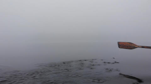 Rowing paddle in dense heavy fog small boat lake in Finland Live Action