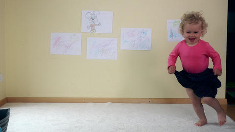 curly baby girl dance on white carpet room. Childhood, game. 4K Live Action