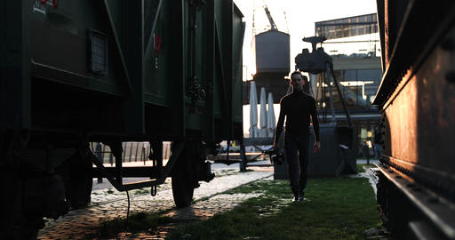 Male filmmaker walk with the camera on sunset in a big city. Industrial Live Action