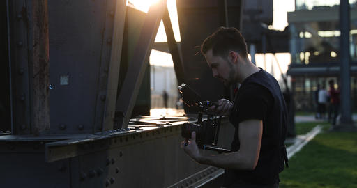Filmmaker film with the camera handheld on sunset in a big city. Industrial Live Action