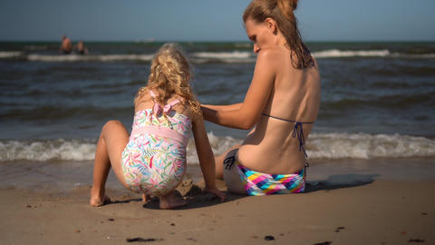 Loving mother with little daughter building castle from wet sand on coastline Live Action