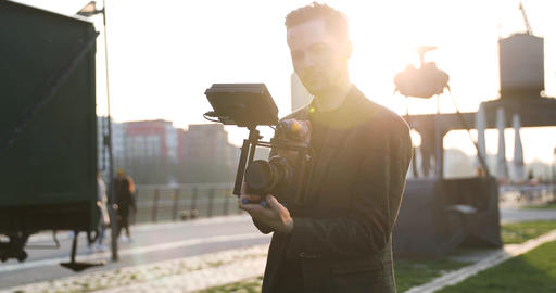 Male Filmmaker smile on to the camera on sunset in a big city. Industrial Live Action
