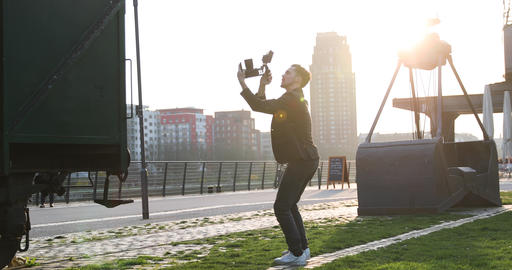 Filmmaker jump with the camera handheld on sunset in a big city. Industrial Live Action
