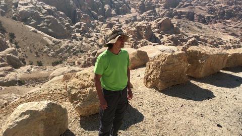 man tourist hiker, standing at desert yellow mountains of jordan, having rest Live Action