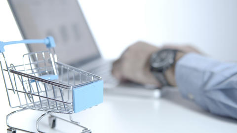 Man use laptop choosing items and buying online in online store with cart on white desk, shopping GIF