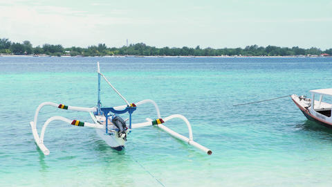 The boat is made of wood and stands in crystal clear sea water on sunny day in Live Action