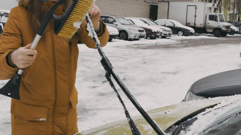 Woman in a warm brown jacket in the yard cleans the windscreen wipers from snow Live Action