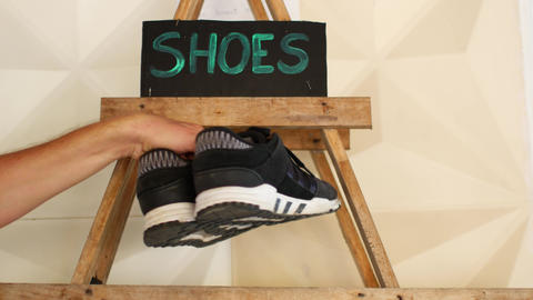 Shelf with shoes, a man changes shoes Live Action
