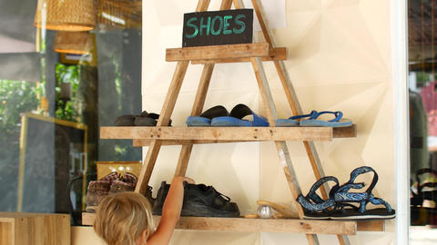Child takes a pair of shoes from a shelf Live Action
