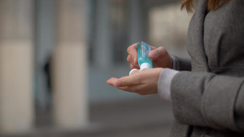 Woman outdoors applying sanitizer Live Action