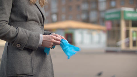 Hands of a woman putting on protective gloves Live Action