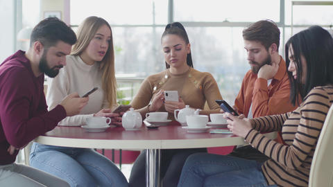 Portrait of five bored Caucasian people sitting in cafe and using smartphones Live Action